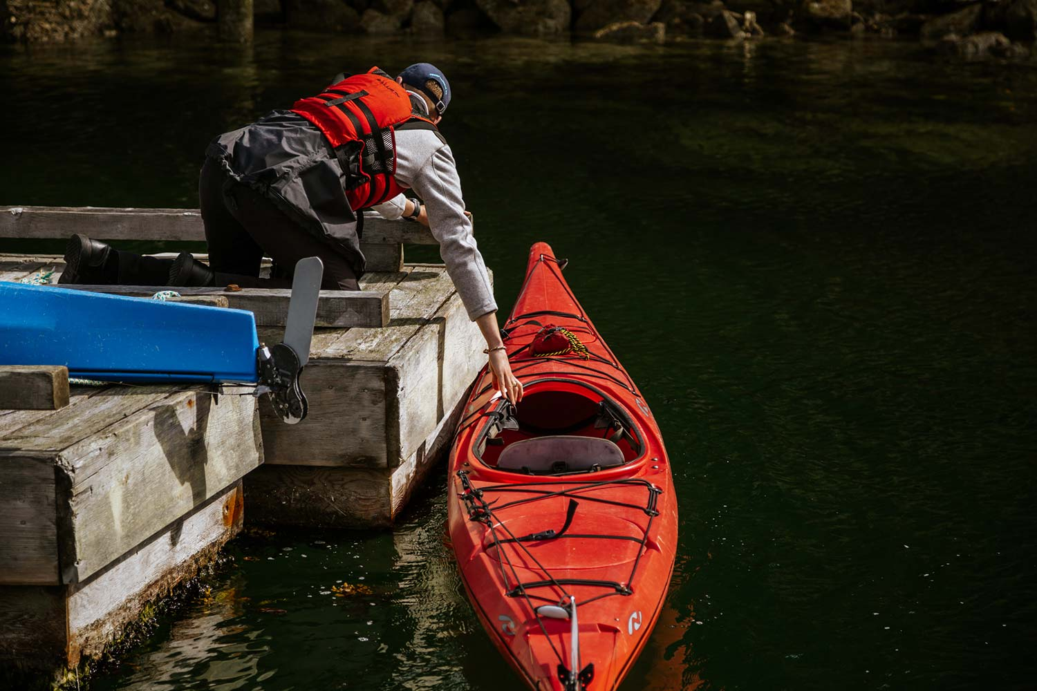 Kayaker gets ready to take his red kayak out into Garden Bay. Kayaking is one of the best activities on the Sunshine Coast, BC.